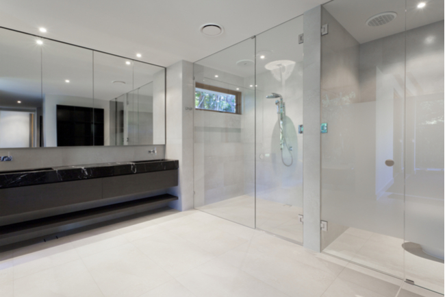 A shower enclosure with clear glass shower doors.